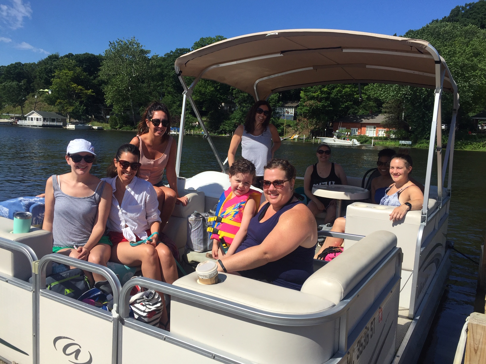 A group enjoying a Pontoon Boat ride on a sunny day in Saugatuck Michigan